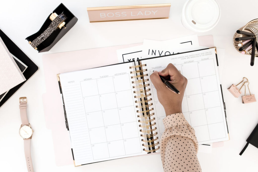 black woman  writing in a planner